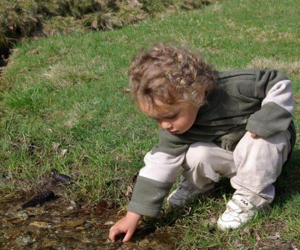 Enfant jouant dans le torrent au parc de Merlet